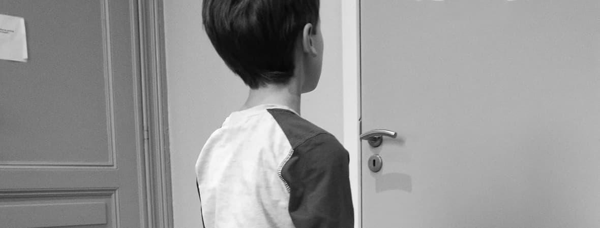 Autisme en Action, petit garçon devant une porte